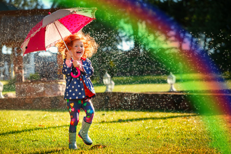 57411018 - laughing girl in the rain under umbrela with a rainbow.
